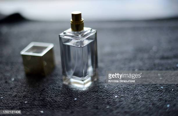 transparent perfume bottle on a sparkly background - kristina strasunske stock pictures, royalty-free photos & images