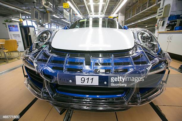Transparent protective casing sits on a Porsche 911 Boxster automobile as it moves along the the production line during assembly at the Porsche AG...