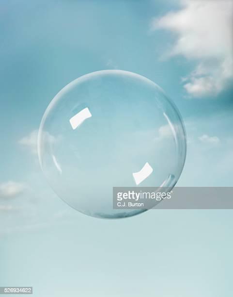 transparent sphere floating in sky - bolla foto e immagini stock