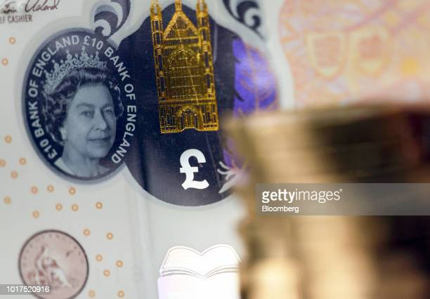 A transparent window featuring a portrait of Queen Elizabeth II sits next to a finely detailed metallic image of Winchester Cathedral and a colored...