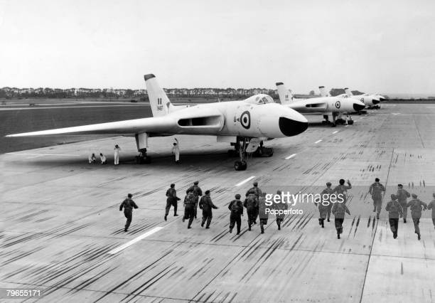 28th August 1960 Scampton Lincolnshire England British Avro 'Vulcan' delta wing jet bombers stand in line as crews run to the planes in an exercise...