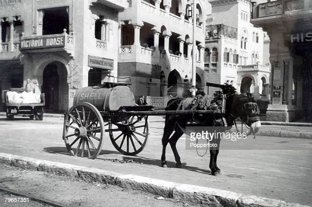 Transport, Cairo, Egypt, Circa 1930's, A dockey pulling a tank of petrol stops on a Cairo street, The tank has Shell written on the side