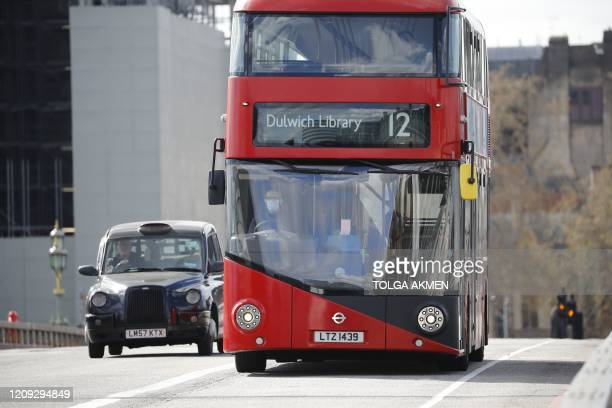 Transport for London London Bus driver, wearing a face mask as a precautionary measure against COVID-19, drives their bus in London on April 6 as...