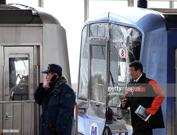 Transport investigators inspect the two trains that collided due to heavy snowing at Tokyu Toyoko line's Motosumiyoshi station in Kawasaki suburban...