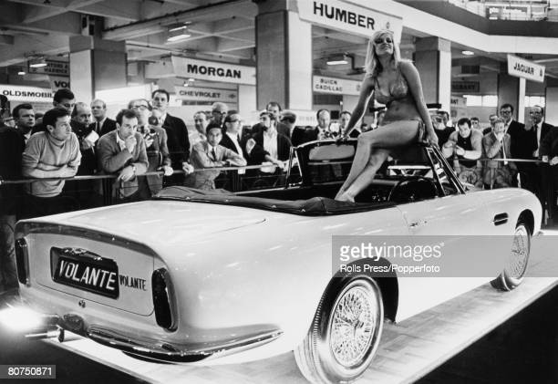Transport London England Model Monika Dietrich sits on top of an Aston Martin Volante sports convertible car at the Earls Court International Motor...