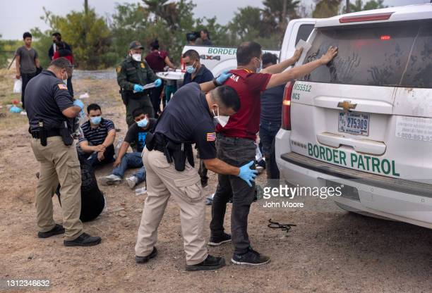 Transport officer searches immigrants before bussing them to a processing center after they crossed the border from Mexico on April 13, 2021 in La...