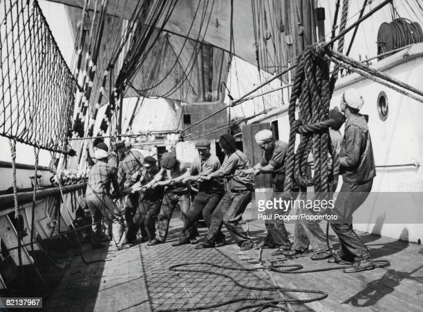 Transport Sailing Ships Merchant Marine Crew members of the fourmasted barque 'Parma' pull at the rope on deck to unfurl the sails during the 'Grain...