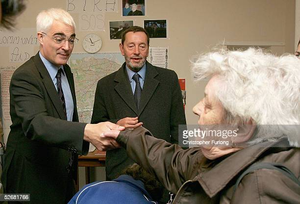 Transport Secretary Alistair Darling and former Home Secretary David Blunkett talk to resident Betty Chirray during a tour of a housing estate on...