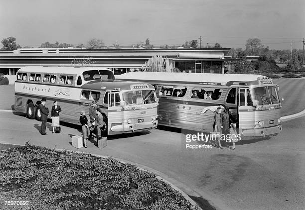 Transport USA Circa 1960's Two Greyhound Express coaches with passengers waiting to board parked at a bus station highway halt