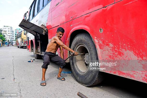 Transport worker seen busy repairing the tire of a bus at the Mohakhali bus terminal. The government has eased the lockdown for a week ahead of Eid....
