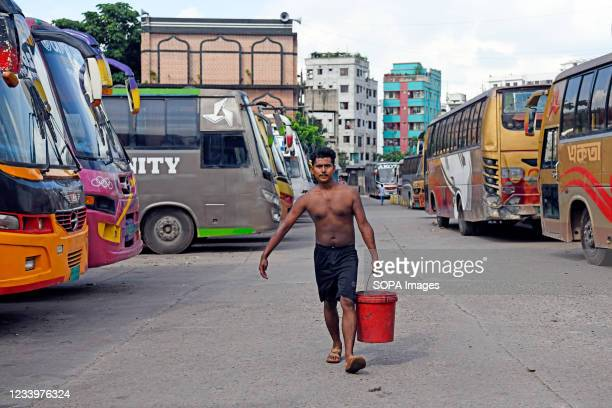 Transport worker seen carrying water for cleaning buses at the Mohakhali bus terminal. The government has eased the lockdown for a week ahead of Eid....