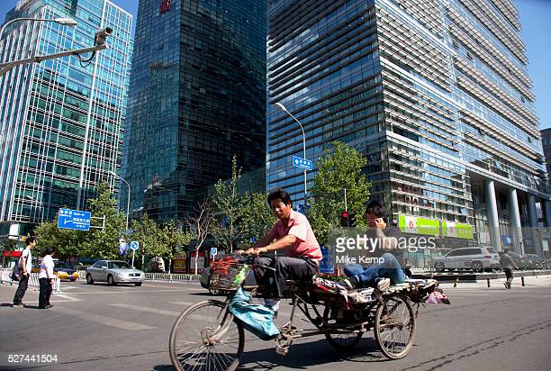 Transport workers passing the shopping malls and offices in Zhongguancun or Zhong Guan Cun a technology hub in Haidian District Beijing China It is...