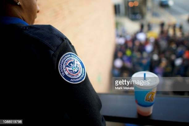 Transportation Authority Administration employee watches fellow TSA employees and other airport workers protest outside the Philadelphia...