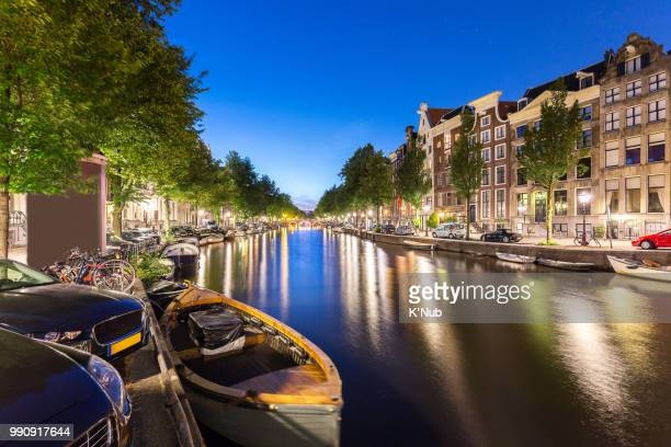 Transportation boat, bicycle, car, and apartment, house, along Amsterdam canal with star on blue clear sky at Netherlands