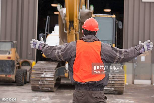 Transportation engineer directing an earth mover at a construction site