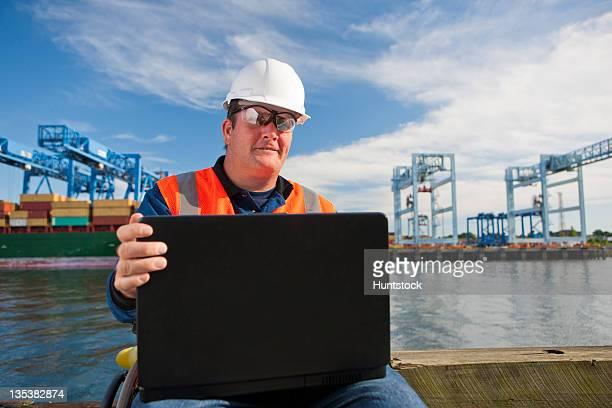 transportation engineer in wheelchair recording data on laptop at shipping port - quadriplegic fotografías e imágenes de stock
