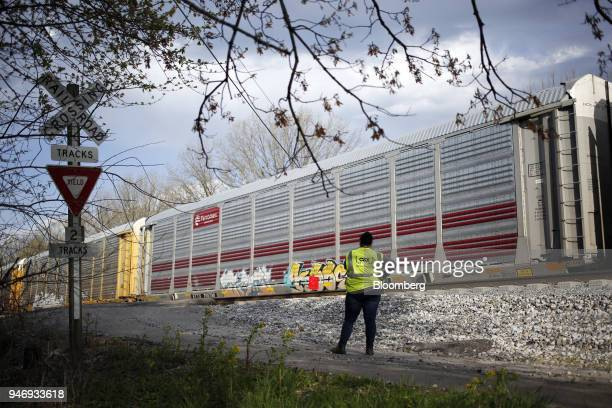 Transportation Inc conductor performs a visual inspection as an autorack train passes on a siding in Bowling Green Kentucky US on Friday April 13...