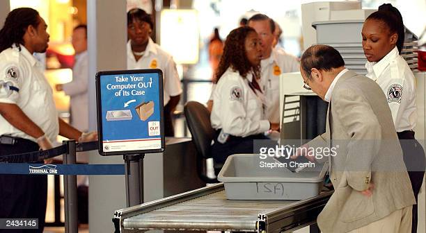 Transportation Safety Administration agents guard a security checkpoint as passengers prepare to pass through the metal detector at John F Kennedy...