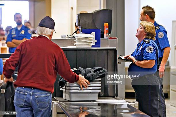 A Transportation Safety Administration officer right operates an xray machine at a security check point at Salt Lake International Airport in Salt...