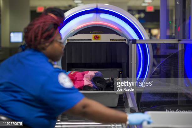 Transportation Security Administration agent helps travelers place their bags through the 3-D scanner at the Miami International Airport on May 21,...