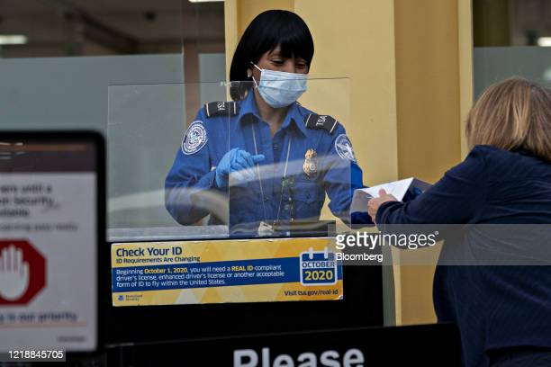 Transportation Security Administration agent wears a protective mask and stands behind a protective barrier while screening a traveler at Ronald...