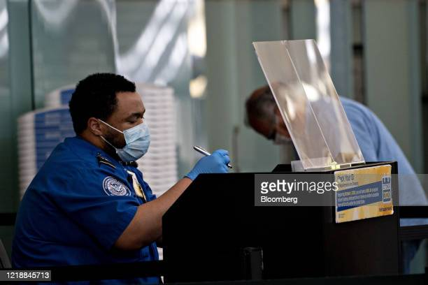 Transportation Security Administration agent wears a protective mask and sits behind a protective barrier while screening a traveler at Ronald Reagan...