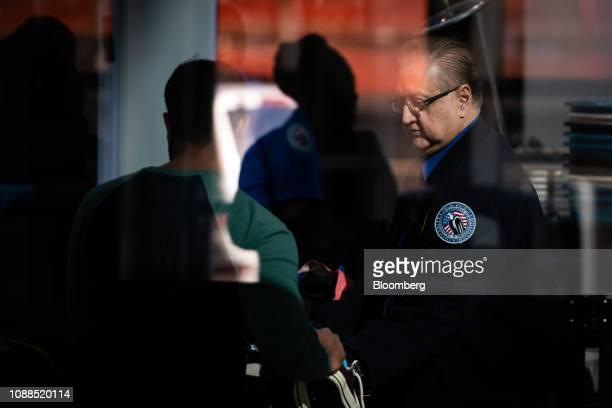 A Transportation Security Administration agent works at a checkpoint at LaGuardia Airport in the Queens borough of New York US on Friday Jan 25 2019...
