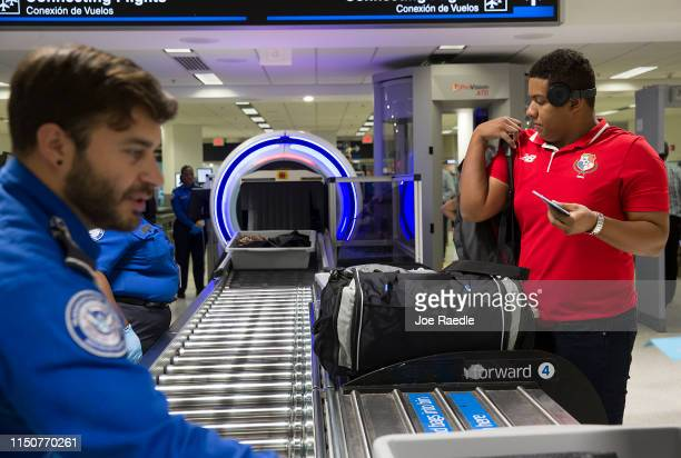 Transportation Security Administration agents help travelers place their bags through the 3D scanner at the Miami International Airport on May 21...