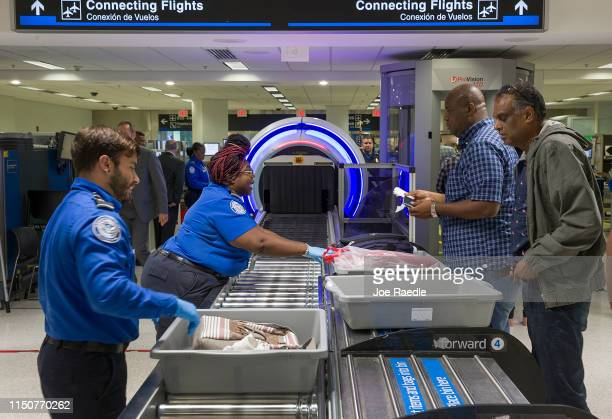 Transportation Security Administration agents help travelers place their bags through the 3-D scanner at the Miami International Airport on May 21,...
