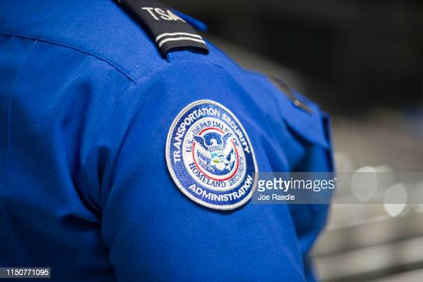 Transportation Security Administration agent's patch is seen as she helps travelers place their bags through the 3-D scanner at the Miami...