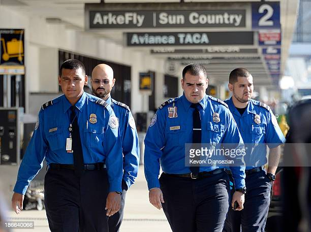 Transportation Security Administration agents walk on the departures level a day after a shooting that killed one Transportation Security...