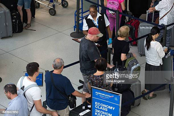 Transportation Security Administration employee checks passenger tickets as they get into the security line at John F Kennedy International Airport...