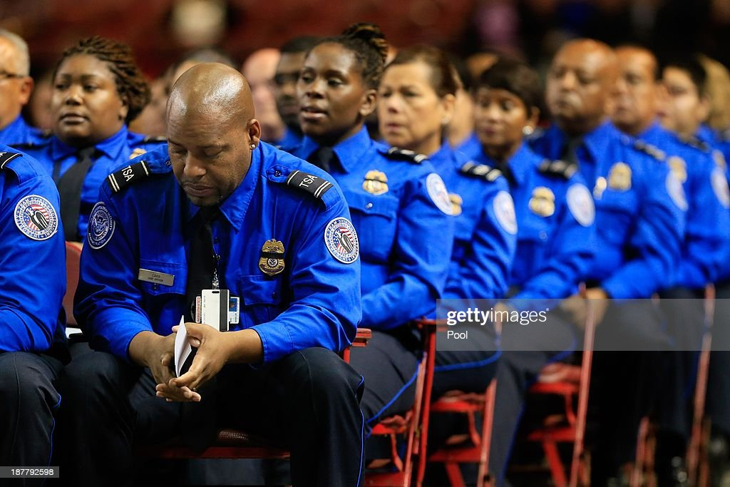 a transportation security administration officer bows his head as he sits alongside colleagues during the public
