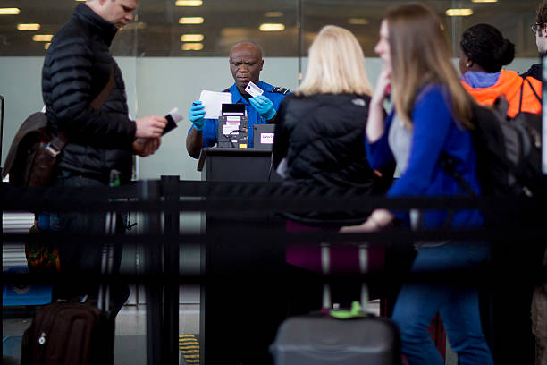 a transportation security administration tsa officer checks a passengers identification and boarding pass at