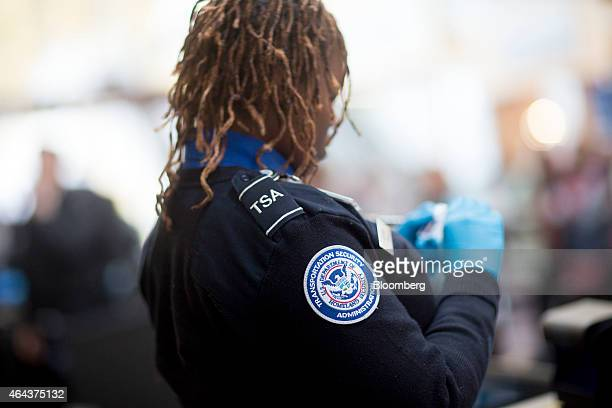 A Transportation Security Administration officer checks a passenger's identification at a security checkpoint at Ronald Reagan National Airport in...