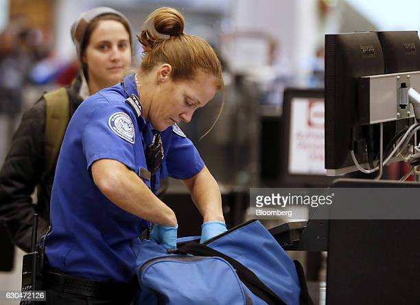 A Transportation Security Administration officer checks a traveler's bag at a screening location at Salt Lake City International Airport in Salt Lake...