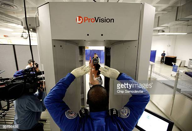 Transportation Security Administration officer guides a person through a 'millimeter wave' scanner during a demonstration at the TSA's Systems...