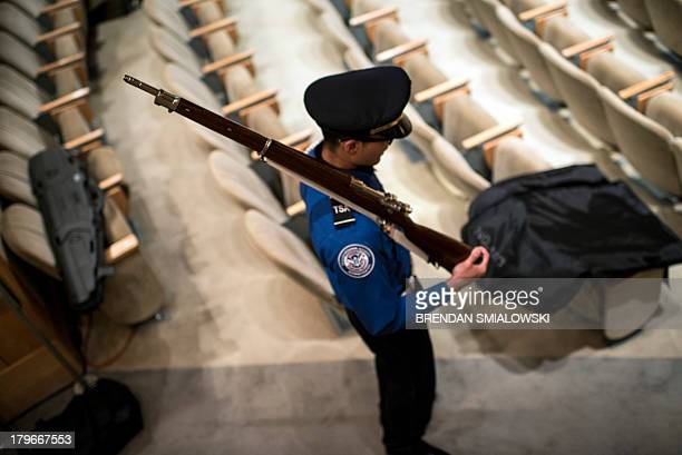 A Transportation Security Administration officer holds a rifle while participating in a color guard before a farewell ceremony for Homeland Security...