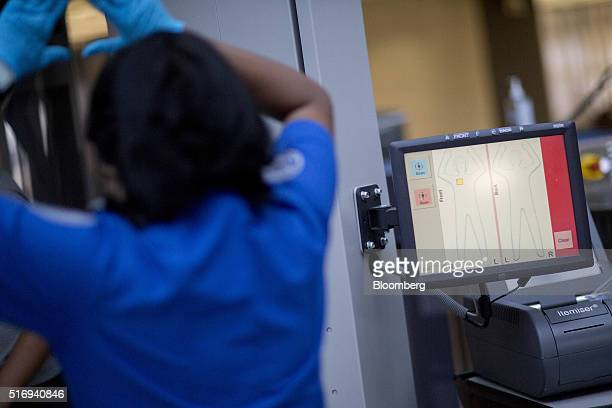 A Transportation Security Administration officer left assists a passenger being screened by an automatic target detection machine in the TSA precheck...