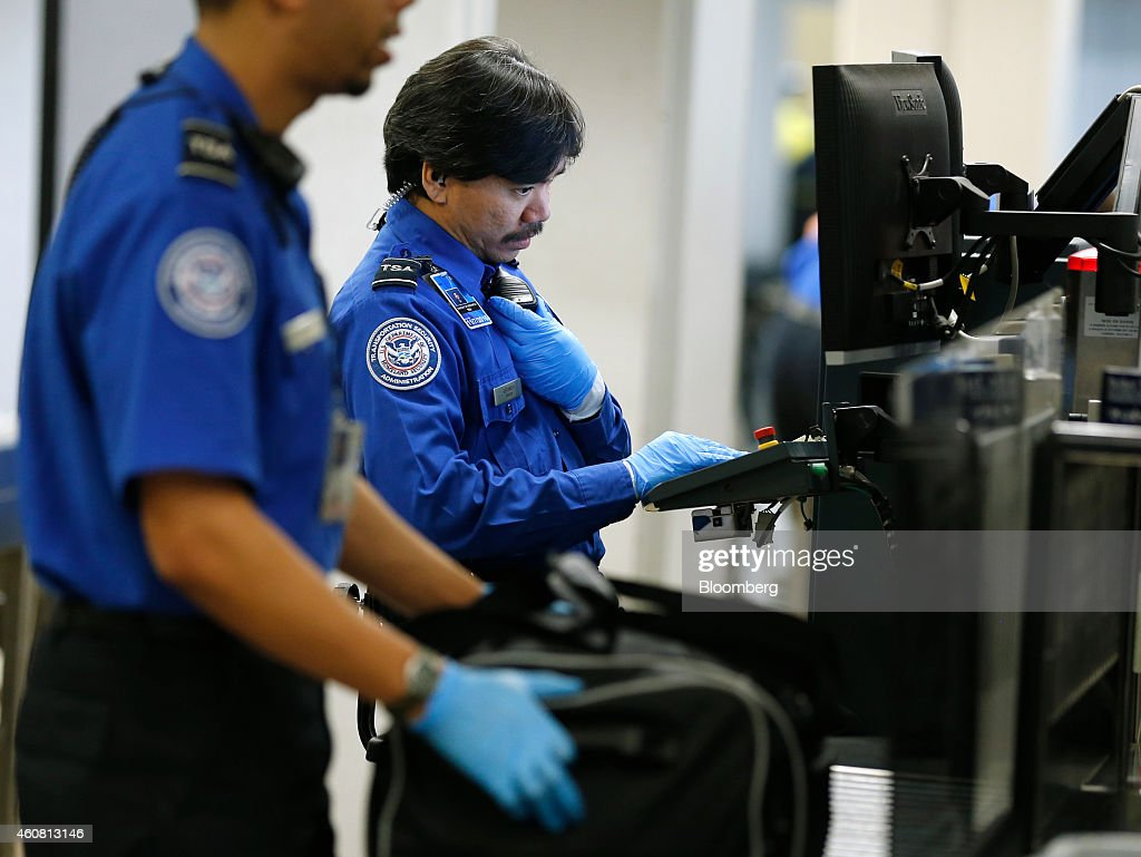 a transportation security administration tsa officer monitors a computer screen as passengers bags - Transportation Security Officer