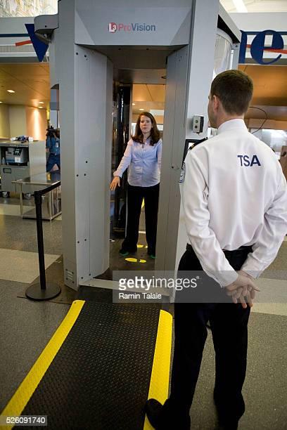 A Transportation Security Administration officer monitors a passenger through a Millimeter Wave Imaging scanner during a pilot program at JFK...