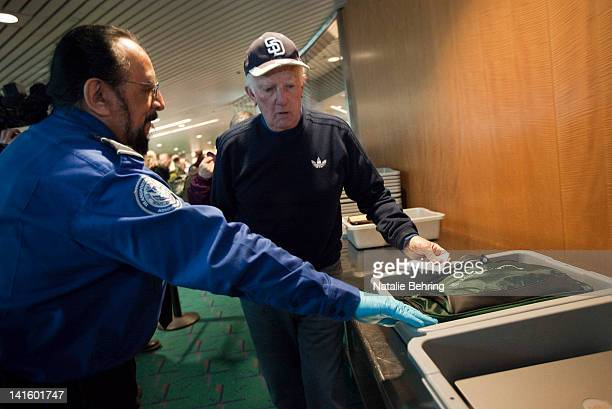 Transportation Security Administration officer Stephen Candia helps an elderly patron pass though a security check at Portland International Airport...