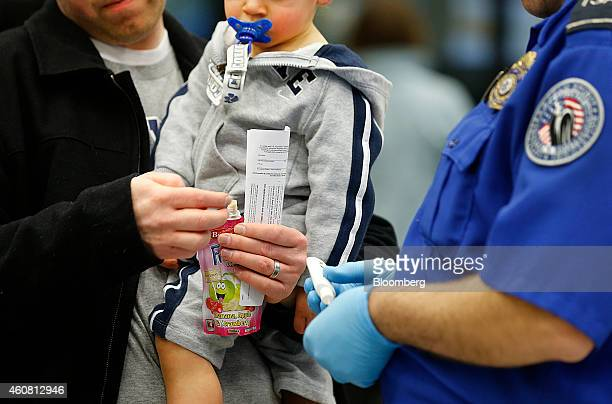 A Transportation Security Administration officer tests child's drink at a security check point at Salt Lake City International Airport in Salt Lake...