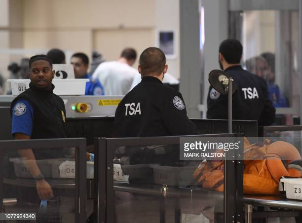 Transportation Security Administration officers stand screen passengers at the departure area of the Los Angeles International Airport in Los Angeles...