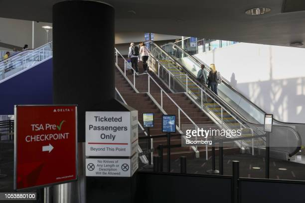A Transportation Security Administration PreCheck sign is displayed outside a as travelers carry baggage at Los Angeles International Airport in Los...