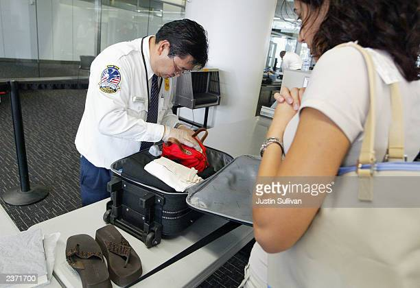 Transportation Security Administration screener inspects a bag at the international terminal of San Francisco International Airport August 5 2003 in...