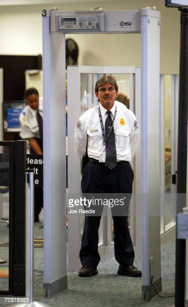 Transportation Security Administration screener waits for passengers to walk through the metal detector at Fort Lauderdale International Airport May...