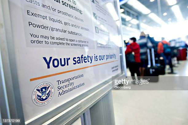 A Transportation Security Administration sign stands as travelers wait to pass through a security check point at O'Hare International Airport in...