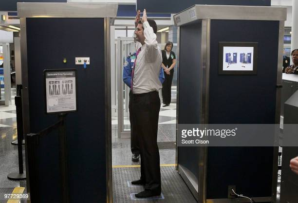 Transportation Security Administration volunteer demonstrates a fullbody scanner at O'Hare International Airport on March 15 2010 in Chicago Illinois...