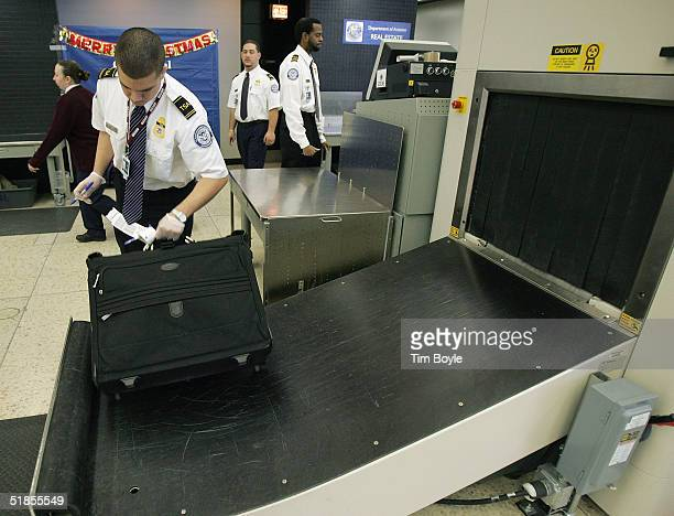 S Transportation Security Administration worker checks baggage after it passed through a CTX explosives screening machine at O'Hare International...